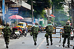 14 MAY 2010 - BANGKOK, THAILAND: Thai troops advance down a side street off of Rama IV Road in Bangkok Friday afternoon. Thai troops and anti government protesters clashed on Rama IV Road Friday afternoon in a series of running battles. Troops fired into the air and at protesters after protesters attacked the troops with rocket and small homemade explosives. Unlike similar confrontations in Bangkok, these protesters were not Red Shirts. Most of the protesters were residents of nearby Khlong Toei slum area, Bangkok's largest slum area. The running battle went on for at least two hours.   PHOTO BY JACK KURTZ