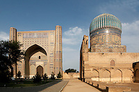 Low angle view of main building, which was used as a huge Mihrab (left) and one of the three domed buildings (right), Bibi-Khanym Mosque, 15th century,  Samarkand, Uzbekistan, pictured on July 16, 2010, at dawn. Named after the wife of Amir Timur, 14th century ruler, the mosque was constructed following his 1399 Indian campaign. It collapsed after an earthquake in 1897 and was restored in the late 20th century. Samarkand, a city on the Silk Road, founded as Afrosiab in the 7th century BC, is a meeting point for the world's cultures. Its most important development was in the Timurid period, 14th to 15th centuries. Picture by Manuel Cohen.