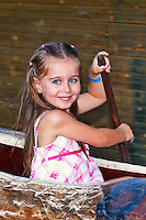 A pretty little girl having fun with canoe