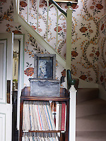 At the bottom of the staircase an antique bookcase contains a collection of vinyl records