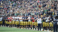 Head coach Brian Kelly and his players stand for the Star-Spangled Banner.