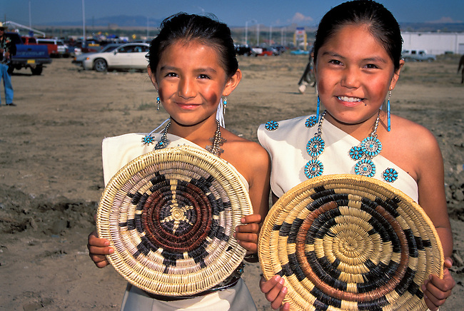 Two young participants of the Naatsiilio (Rainbow) Dancers are dressed in traditional Navajo cotton dresses adorned with turquoise and wearing Navajo moccasins and leggings hold traditional baskets