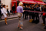 Motcomb Street, street party Belgravia London 1998. Sophie Dahl cutting red tape to open party. PR watching from side