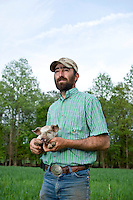 Jeremiah Jones and one of his new piglets at Beaulaville, NC pig farm - Grassroots Pork Co.