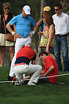 A little bit of TLC for one of the spectators as Simon Dyson manages to take out a spectator on the 6th when his ball hit the man on the left knee.on day one of the Omega Dubai Desert Classic 2011 on the Majlis Course, Emirates Golf Club, Dubai, UAE. 10/02/2011.Picture Fran Caffrey/www.golffile.ie.