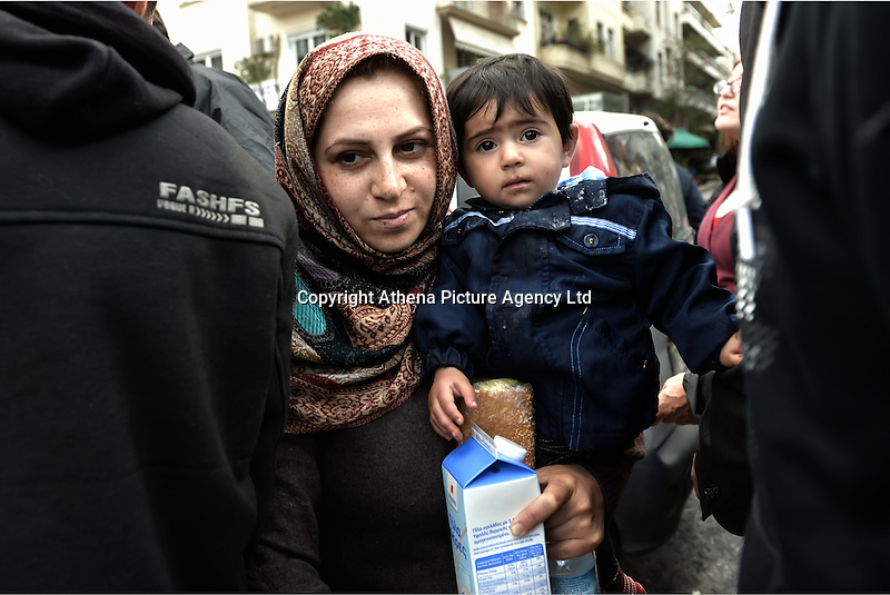 Pictured: A young mother clutches her young son after being given food and milk Friday 26 February 2016<br /> Re: Hundreds of refugees have temporarily camped at Victoria Square in central Athens, Greece.