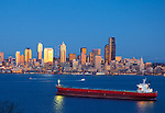 Seattle, Washington<br /> Dusk on Elliott Bay with red container ship and passing  boats with Seattle city skyline glowing in reflected light