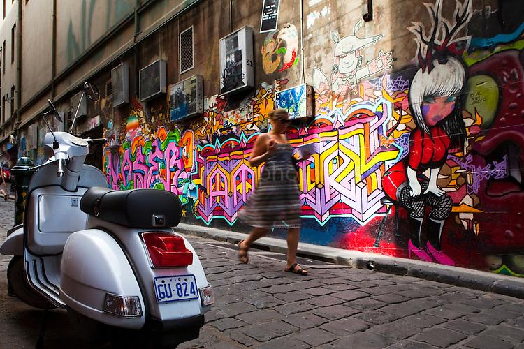 Girl walking down Hosier Lane, beside Graffiti and moped, Melbourne
