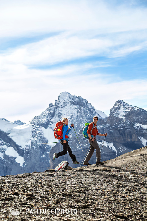 A couple hiking in the Swiss Alps, laughing as the woman jumps high into the air