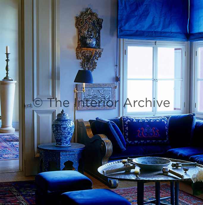 The blue sitting room is furnished with a velvet-covered banquette and matching pouffes