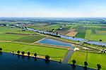 Nederland, Noord-Brabant, Gemeente Waspik, 23-08-2016; Overdiepsche polder: in het kader van het programma 'Ruimte voor de Rivier' (bescherming tegen hoogwater door rivierverruiming), is de dijk langs de Bergsche Maas (onder in beeld) verlaagd. Bij hoogwater kan de Overdiepse polder overstromen. De boerderijen in de polder zijn gesloopt en verplaatst naar de dijk van het Oude Maasje. De nieuwe boerderijen met bijgebouwen staan op terpen.<br /> Depoldering of Overdiep Polder, farms are relocated and built on mounds. This makes it possible for the river to overflow the polder in case of heigh waters.<br /> luchtfoto (toeslag op standard tarieven);<br /> aerial photo (additional fee required);<br /> copyright foto/photo Siebe Swart