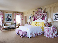 In the master bedroom, the table lamps and iron curtain poles and bed frame, which are draped with a toile de Jouy, are by Andrew Fisher, the stools are upholstered in a Manuel Canovas fabric, and the sofa and Getty-designed chairs are covered in muslin. The photographs are by Jackie Nickerson