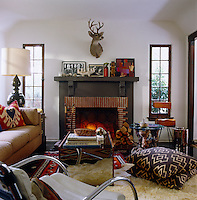 A lit fire in the fireplace is flanked by a pair of long and narrow windows in this cosy living room