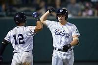 Ryder Green (right) of the Pulaski Yankees bumps forearms with teammate Jesus Bastidas (12) after hitting a home run against the Burlington Royals at Calfee Park on August 31, 2019 in Pulaski, Virginia. The Yankees defeated the Royals 6-0. (Brian Westerholt/Four Seam Images)