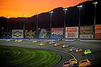 Aug 31, 2008; Fontana, CA, USA; NASCAR Sprint Cup Series drivers race through turn two as the sun sets during the Pepsi 500 at Auto Club Speedway. Mandatory Credit: Mark J. Rebilas-