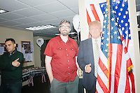 Photographer M. Scott Brauer poses next to a cardboard cut-out of Republican presidential nominee Donald Trump in the Palm Beach Republican Club and West Palm Beach Victory Headquarters office in West Palm Beach, Florida. The office serves as a place for volunteers to gather and organize for various Republican campaigns, including Donald Trump's general election campaign.