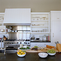The large range and hood in the kitchen are by Viking and cake stands and silverware are displayed on the open shelves