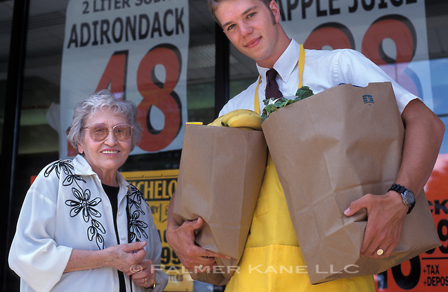 Part time grocery clerk assists senior woman with her grocery bags