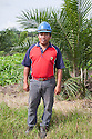 Portrait of a Malay palm plantation worker in field. The Sindora Palm Oil Plantation, owned by Kulim, is green certified by the Roundtable on Sustainable Palm Oil (RSPO) for its environmental, economic, and socially sustainable practices. Johor Bahru, Malaysia