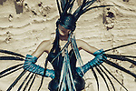 Young woman wearing corset and mask with long feathers