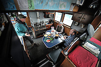 From left, Dan Logan, John DeLapp and Joe Flynn hold a discussion over lunch in the galley of the M/V Auklet, a 58-foot wooden research vessel, after departing from the town of Cordova, Prince William Sound, Southcentral Alaska on a spring day in early May. MR/PR