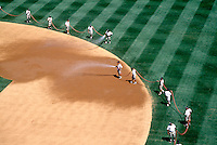 WORKERS WATERING A  BASEBALL STADIUM<br /> To Control Dust on Base Path<br /> Groundskeepers prepare the Yankee Stadium right before the start of the game.