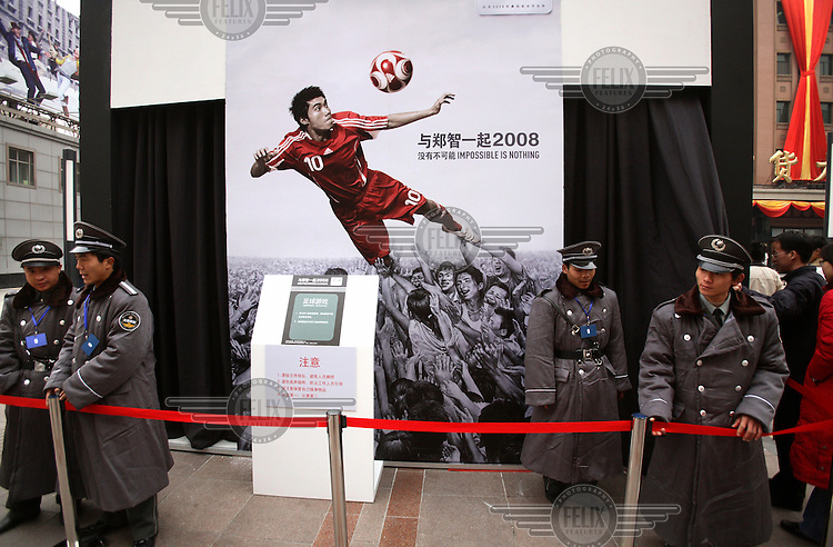 2008 Olympic Games poster, featuring a Chinese football player, stands behind guards protecting one of the stands during an Adidas promotional event.