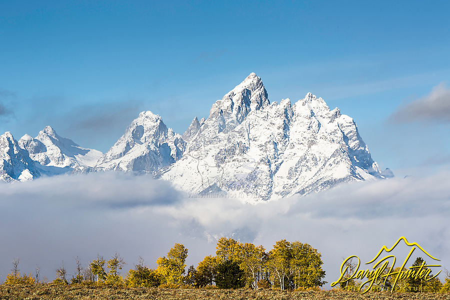 A bit of autumn and a bit of winter, a very grand Grand Teton rises above the valley of Jackson Hole in Grand Teton National Park