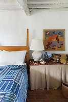 A guest bedroom has a rustic simplicity. Traditional local materials were kept during the restoration of the house, such as the terracotta tiles on the floor and ceilings and the original massive wooden beams.