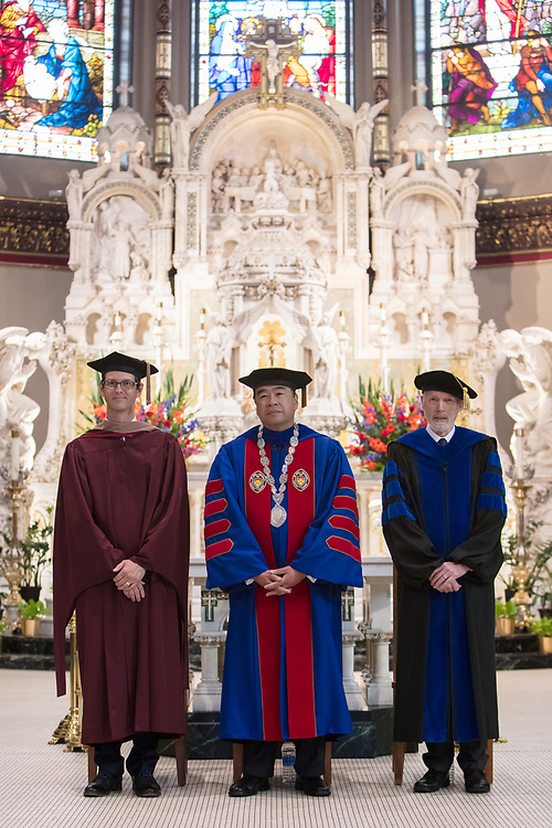 Left to right, Jeff Bethke, executive vice president, A. Gabriel Esteban, Ph.D., president, and Marten denBoer, provost, stand as faculty and staff enter into the St. Vincent de Paul Parish Church for the annual Academic Convocation ceremony, Thursday, Aug. 31, 2017, on the Lincoln Park Campus. (DePaul University/Jeff Carrion)