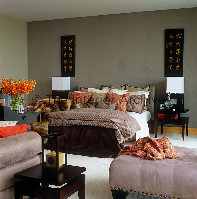 Lending a touch of luxury to this bedroom of a London apartment taupe velvet has been used as a wallcovering behind the double bed whilst tweed and cashmere scatter cushions in shades of orange add bright notes of colour