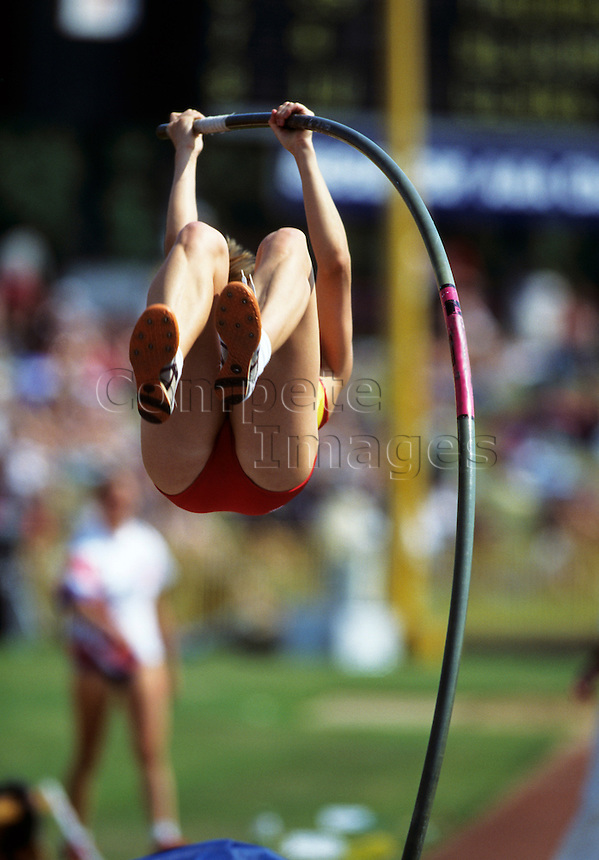Female pole vaulter bends bar as she attempts a clearance at track