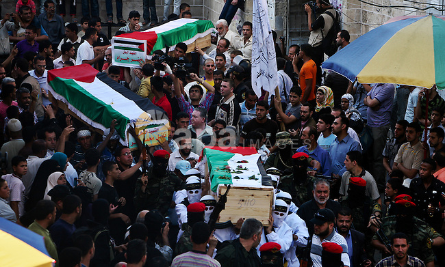 Relatives and masked Palestinian militants carry flag-drapped coffins containing the remains of Palestinian militants after the arrival of the caskets in Gaza City, 31 May 2012. Israel handed over the remains of dozens of militants to the Palestinians, saying it hoped the 'goodwill gesture' would help restart peace talks. Exhumed from enemy cemeteries in Israel, 79 were transported to the central West Bank city of Ramallah and 12 to the Gaza Strip, for reburial in their respective hometowns.  Photo by Ali Jadallah