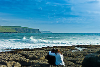 Young couple courting on rocks at Doolin view the Cliffs of Moher, County Clare, West Coast of Ireland