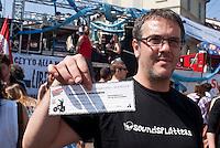 """Milano, Mayday Parade, manifestazione del 1. maggio di gruppi e organizzazioni di sinistra contro il lavoro precario. Emilio Daniele detto """"Face"""", candidato del centro sociale Leoncavallo a sostegno di Pisapia alle elezioni amministrative, con un finto """"assegno precario"""" da mille euro per promuovere il reddito di cittadinanza --- Milan, Mayday Parade, 1st of May manifestation of leftist groups and organizations against temporary work. Emilio Daniele also called """"Face"""", candidate of Leoncavallo social center in support of Pisapia for local elections, holds a fake """"precarious check"""" by a thousand euro to promote basic income"""