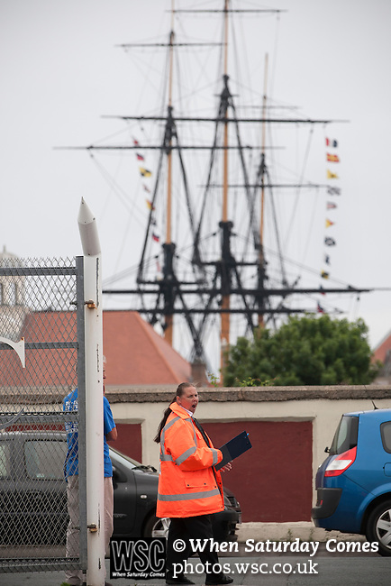 Hartlepool United 0 Middlesbrough 0, 20/07/2013. Victoria Ground, Pre-Season Friendly. The Trincomalee, an historic floating warship permanently moored in Hartlepool marina, provides the backdrop as a steward regulates the car parking at the Victoria Ground, Hartlepool, before the pre-season friendly between Hartlepool United and Middlesbrough. Hartlepool were relegated to League Two at the end of the 2012-13 season whilst their Teesside neighbours remained two divisions above them in the Championship. The game ended in a no-score draw watched by a crowd of 2307. Photo by Colin McPherson.
