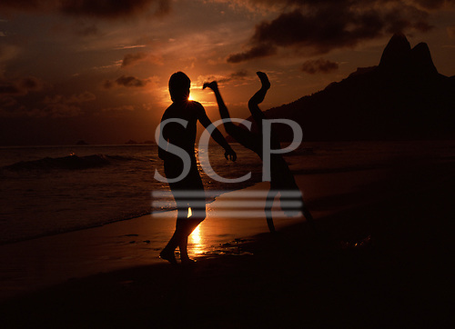 Rio de Janeiro, Brazil. Two youths practising capoeira on the beach at sunset with the Dois Irmaos mountain behind.
