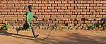 A boy runs as he rolls a bicycle wheel in front of a house in Kaluhoro, Malawi. With support from the Ekwendeni Hospital AIDS Program, members of his family and other families in the village are participating in a Building Sustainable Livelihoods program, working together to earn and save money, raise more nutritious food, and receive vocational training.