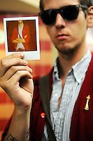 Joey Loran of Seattle holds a Polaroid photo depicting the red cardigan, striped shirt and Space Needle pin he wore to the 2011 Bumbershoot music and arts festival in Seattle Center on Monday, September 5, 2011. Loran said that everything he was wearing had come from some of the many shopping trips he's made to the Puyallup Value Village.