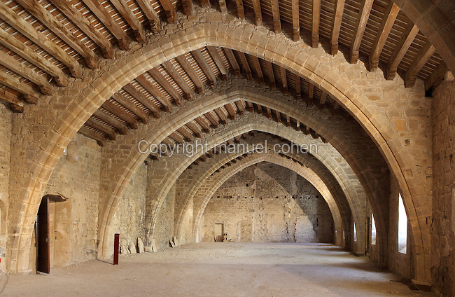 Huge dormitory built in the late 13th century at the Abbey of St Mary of Lagrasse, Aude, Languedoc-Roussillon, France. The room, on the first floor, measures 500m2 and its wooden ceiling beams are held in place with stone arches along its length. Picture by Manuel Cohen