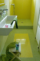 The walls and floor of this narrow shower room are lined with acid yellow and green mosaic tiles by Bisazza