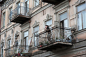 Young woman speaks on a mobile phone on the balcony of an apartment building in Tbilisi.