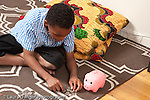 8 year old boy sitting on floor counting sorting coins piggy bank nearby horizontal