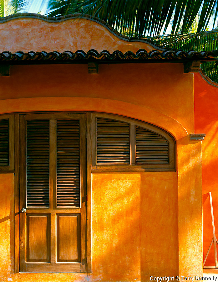 Nayarit, Mexico: Afternoon light rakes the woodend doorway and orange walls of a courtyard in the village of Bucerias