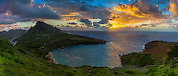 The rising sun casts sun rays into the sky and a reflection on the ocean leading into Hanauma Bay, with Koko Crater on the lest, East O'ahu.