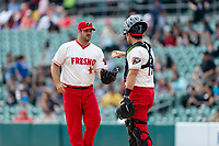 Fresno Grizzlies catcher Taylor Gushue (19) hands the ball to relief pitcher JJ Hoover (35) pitches during a game against the Reno Aces at Chukchansi Park on April 8, 2019 in Fresno, California. Fresno defeated Reno 7-6. (Zachary Lucy/Four Seam Images)