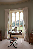 An elegant Regency dressing table framed by a gothic window over looking the garden