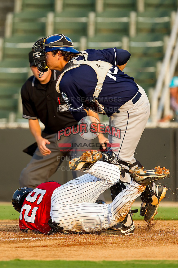 Catcher Anthony Aguilera #16 of the Asheville Tourists holds on to the baseball after tagging out Carlos Sanchez #29 of the Kannapolis Intimidators as home plate umpire Jansen Visconti looks on at Fieldcrest Cannon Stadium on July 28, 2011 in Kannapolis, North Carolina.   (Brian Westerholt / Four Seam Images)