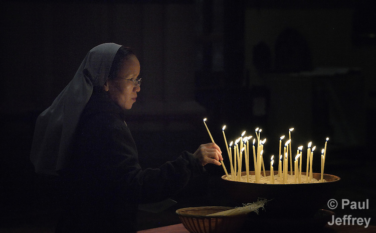 Hien Nguyen, a Catholic nun from Vietnam, lights candles at a July 22, 2014, interfaith service at St. Paul's (Anglican) Cathedral in Melbourne, Australia. The event was a memorial service for those who have died of HIV and AIDS-related causes, and included the involvement of several delegates to the 20th International AIDS Conference. The service came following a march through Melbourne demanding an end to stigma and discrimination against those living with the virus, and a candlelight service in a nearby plaza.