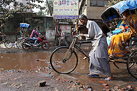 Pedestrians, bikes and motorbikes mix on a flooded street in Kolkata.<br /> <br /> To license this image, please contact the National Geographic Creative Collection:<br /> <br /> Image ID: 1925760 <br />  <br /> Email: natgeocreative@ngs.org<br /> <br /> Telephone: 202 857 7537 / Toll Free 800 434 2244<br /> <br /> National Geographic Creative<br /> 1145 17th St NW, Washington DC 20036